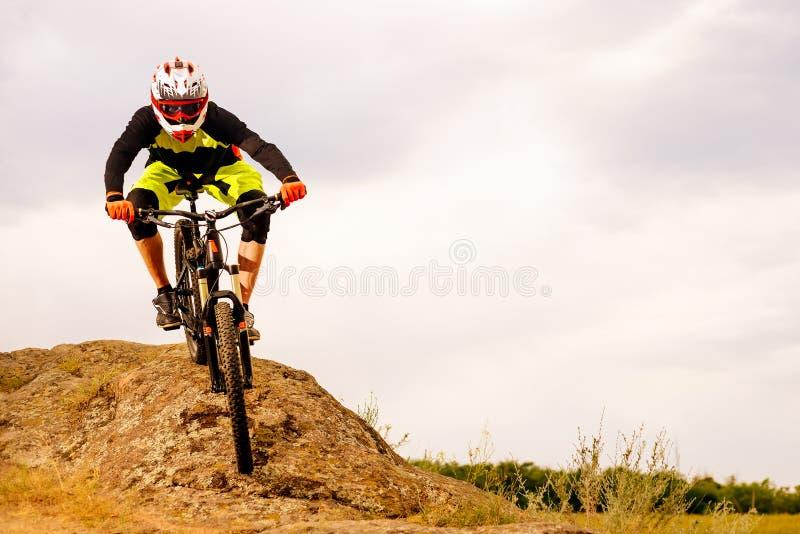 Επαγγελματικός ποδηλάτης που οδηγά το ποδήλατο κάτω από το δύσκολο Hill Ακραία αθλητική έννοια Διάστημα για το κείμενο στοκ φωτογραφία με δικαίωμα ελεύθερης χρήσης