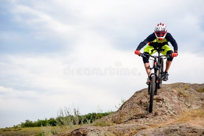 Επαγγελματικός ποδηλάτης που οδηγά το ποδήλατο κάτω από το δύσκολο Hill Ακραία αθλητική έννοια Διάστημα για το κείμενο στοκ εικόνες