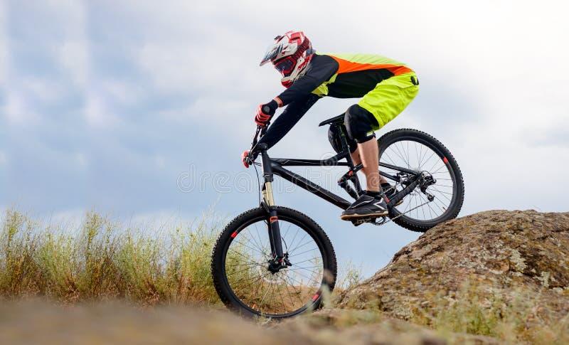 Επαγγελματικός ποδηλάτης που οδηγά το ποδήλατο κάτω από το δύσκολο Hill Ακραία αθλητική έννοια Διάστημα για το κείμενο στοκ φωτογραφίες