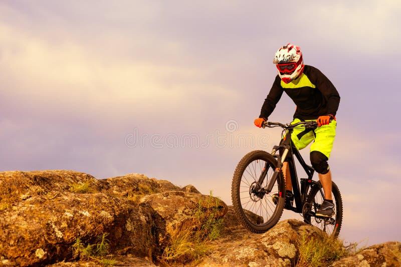 Επαγγελματικός ποδηλάτης που οδηγά το ποδήλατο στην κορυφή του βράχου Ακραία αθλητική έννοια Διάστημα για το κείμενο στοκ φωτογραφίες