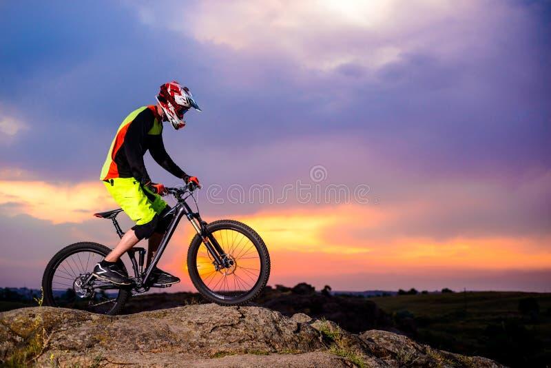 Επαγγελματικός ποδηλάτης που οδηγά το ποδήλατο στο βράχο στο ηλιοβασίλεμα Ακραία αθλητική έννοια Διάστημα για το κείμενο στοκ φωτογραφία με δικαίωμα ελεύθερης χρήσης