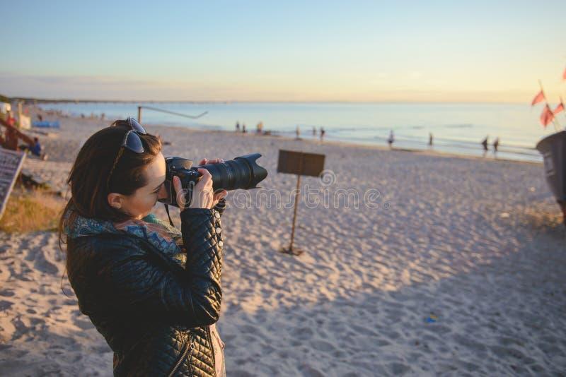 επαγγελματικός φωτογράφος γυναικών στην παραλία στοκ φωτογραφία