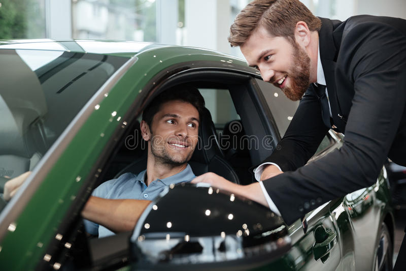 Επαγγελματικό αρσενικό πωλώντας αυτοκίνητο εμπόρων σε έναν πελάτη στοκ εικόνα με δικαίωμα ελεύθερης χρήσης