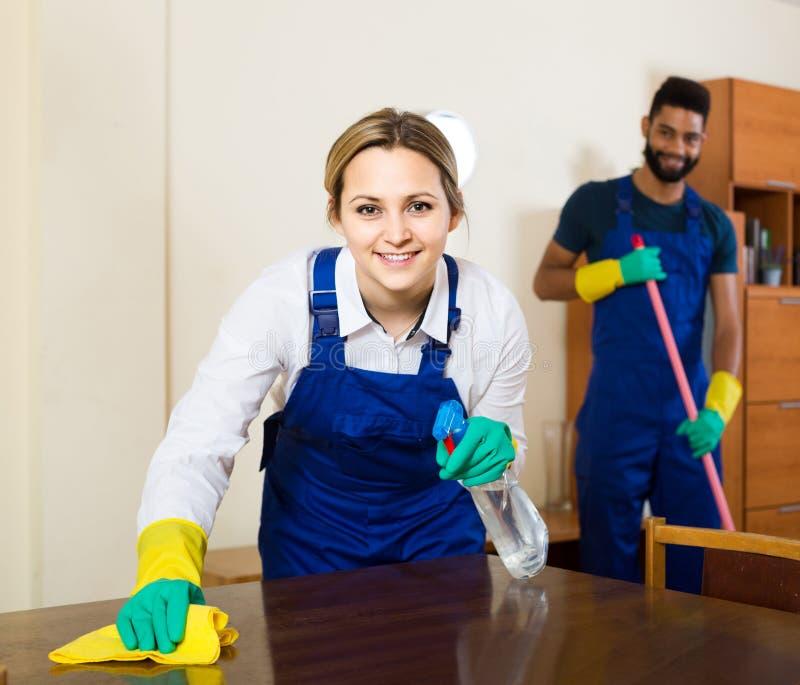Επαγγελματικό ζεύγος στον ομοιόμορφο καθαρισμό στο εσωτερικό εσωτερικό στοκ φωτογραφία
