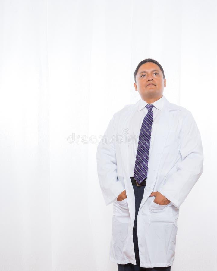 Επαγγελματικό ισπανικό αρσενικό φορώντας παλτό εργαστηρίων στοκ εικόνα