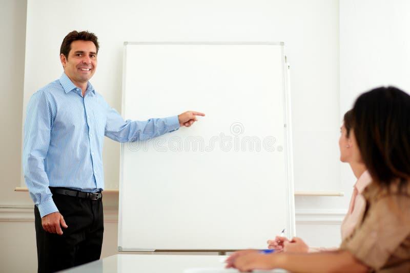 Επαγγελματικό όμορφο άτομο που δείχνει στο whiteboard στοκ εικόνα με δικαίωμα ελεύθερης χρήσης