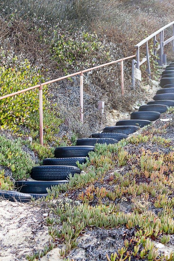 Επαναχρησιμοποίηση των φορεμένων ροδών ως βήματα, που γεμίζουν με την άμμο, κιγκλίδωμα, με τις εγκαταστάσεις βουνοπλαγιών στοκ φωτογραφία με δικαίωμα ελεύθερης χρήσης