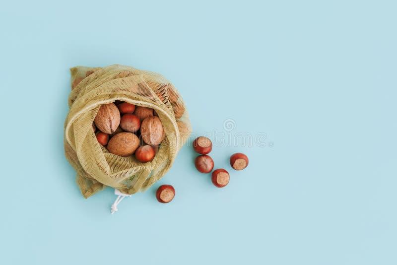 Επαναχρησιμοποιήσιμη τσάντα με τα καρύδια στο μπλε υπόβαθρο Μηά απόβλητα και πλαστική ελεύθερη έννοια αγορών στοκ εικόνα