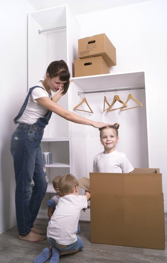 Επανεντοπισμός: Το Mom και τα παιδιά ανοίγουν τα κιβώτια στο καινούργιο σπίτι στοκ εικόνες με δικαίωμα ελεύθερης χρήσης