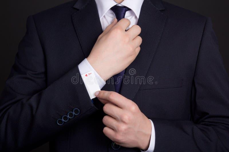 Επανδρώνει τον κρύβοντας άσσο χεριών στο μανίκι κοστουμιών στοκ φωτογραφίες