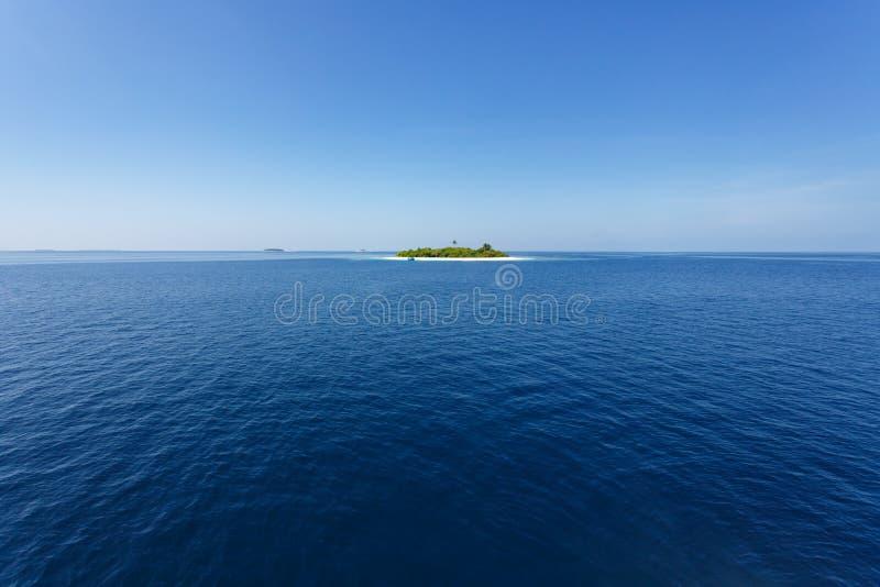 Επεκτατικός μπλε ωκεανός με ένα μικρό τροπικό νησί στοκ φωτογραφία