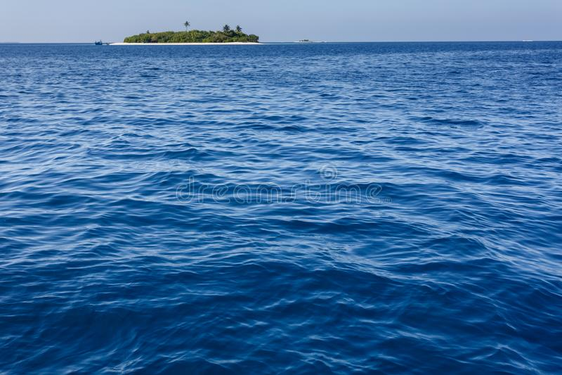 Επεκτατικός μπλε ωκεανός με το μικρό τροπικό νησί με τους φοίνικες που αντιμετωπίζονται στην απόσταση στοκ εικόνα