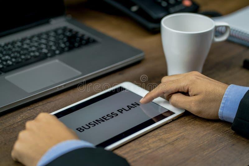 Επενδυτής ή επιχειρησιακό άτομο που αναθεωρεί ή που ελέγχει το επιχειρηματικό σχέδιο στοκ εικόνα