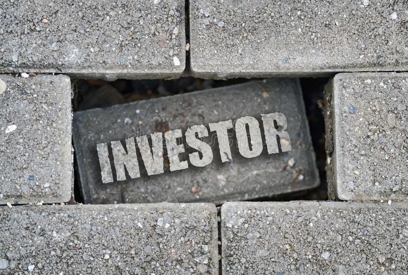 Επενδυτής λέξης πέρα από ένα τούβλο στοκ εικόνες