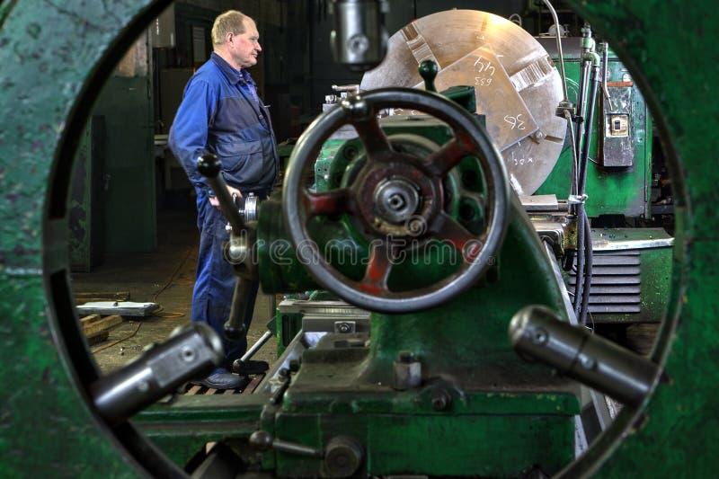 Επεξεργασία μετάλλων στο μεγάλο τόρνο, έλεγχος χειριστών μηχανών τορναδόρων στοκ φωτογραφίες