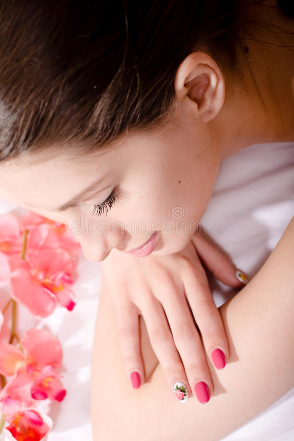 επεξεργασία SPA: όμορφη νέα ελκυστική γυναίκα brunette με το λουλούδι, ρόδινη εικόνα μανικιούρ στοκ φωτογραφία με δικαίωμα ελεύθερης χρήσης