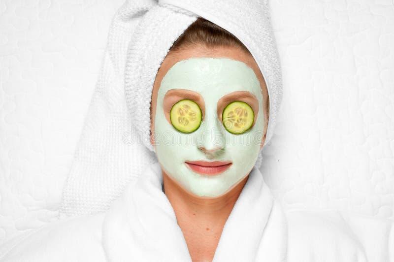 Επεξεργασίες ομορφιάς Γυναίκα που εφαρμόζει την του προσώπου μάσκα αργίλου στη SPA στοκ φωτογραφίες