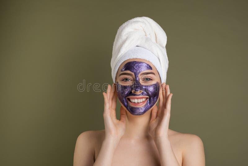 Επεξεργασίες προσοχής και ομορφιάς προσώπου Ευτυχής γυναίκα με την πορφυρή ενυδατική μάσκα υφασμάτων στο πρόσωπό της στοκ εικόνα με δικαίωμα ελεύθερης χρήσης