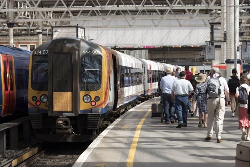 Επιβάτες και ένα τραίνο σιδηροδρόμων στο Λονδίνο στοκ φωτογραφίες