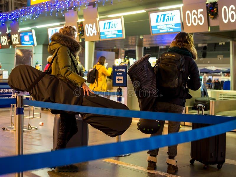 Επιβάτες με τον κατάλογο για το χειμερινό αθλητισμό που αναμένει την εγγραφή στον αερολιμένα Vnukovo στοκ εικόνες
