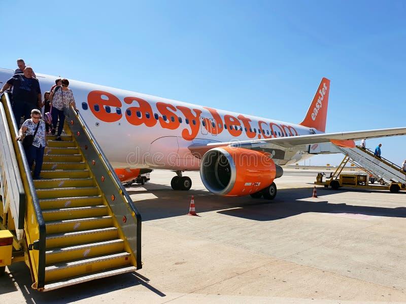 Επιβάτες που επιβιβάζονται από το αεροπλάνο και τον τίτλο προς τη συλλογή αποσκευών στοκ εικόνες