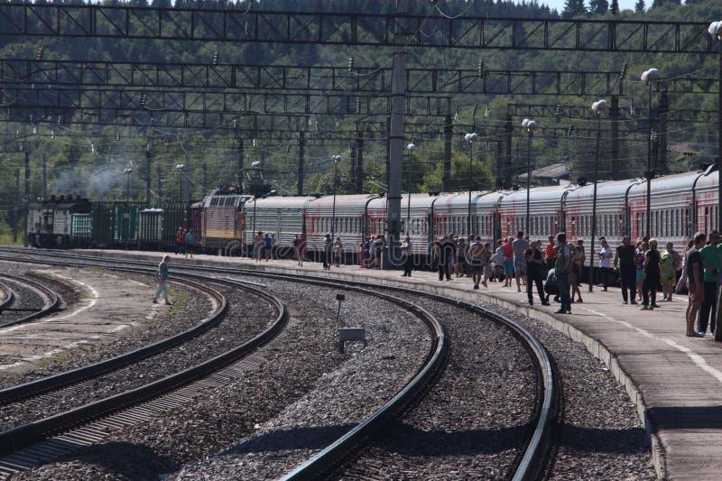 Επιβάτες που περιμένουν στην πλατφόρμα δίπλα στο τραίνο, που σταματούν στο σταθμό στοκ φωτογραφίες με δικαίωμα ελεύθερης χρήσης
