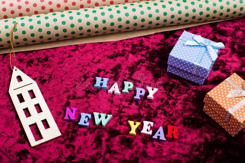 Επιγραφή & x22 Καλή χρονιά & x22  στο υπόβαθρο βελούδου, τις διακοσμήσεις Χριστουγέννων, τα κιβώτια δώρων και τυλίγοντας χαρτί στοκ φωτογραφίες