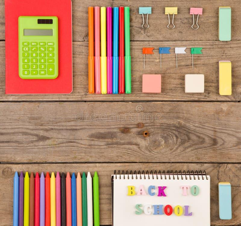 επιγραφή & x22 πίσω στο school& x22 , υπολογιστής, σημειωματάρια, δείκτες και άλλα χαρτικά στον καφετή ξύλινο πίνακα στοκ εικόνες με δικαίωμα ελεύθερης χρήσης