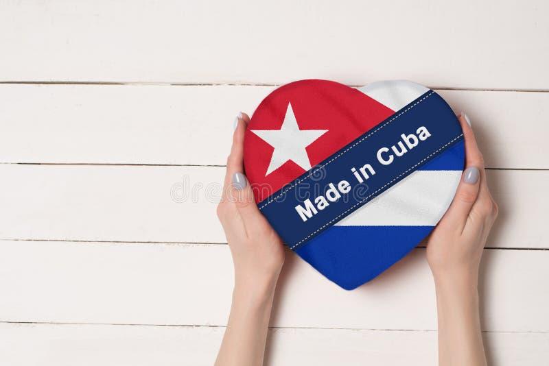 Επιγραφή που κατασκευάζεται στην Κούβα, η σημαία της Κούβας Θηλυκά χέρια που κρατούν ένα διαμορφωμένο καρδιά κιβώτιο Άσπρος ξύλιν στοκ εικόνα