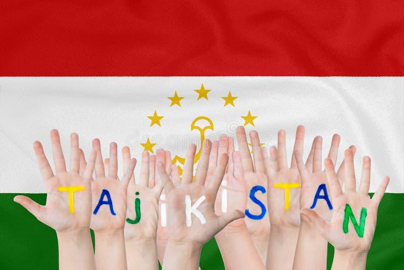 Επιγραφή Τατζικιστάν σε ετοιμότητα των παιδιών στα πλαίσια μιας κυματίζοντας σημαίας του Τατζικιστάν στοκ εικόνες