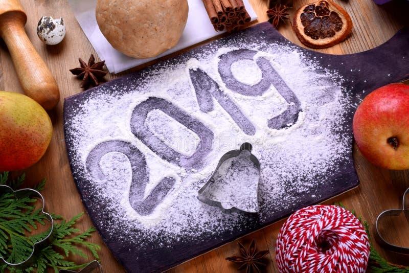 επιγραφή του 2019 σε έναν ψεκασμένο αλεύρι πίνακα, τις φόρμες μπισκότων Χριστουγέννων και τα συστατικά στοκ εικόνες με δικαίωμα ελεύθερης χρήσης