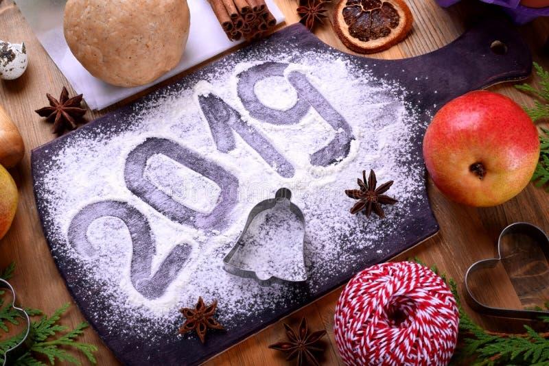 επιγραφή του 2019 σε έναν ψεκασμένο αλεύρι πίνακα, τις φόρμες μπισκότων Χριστουγέννων και τα συστατικά στοκ φωτογραφίες με δικαίωμα ελεύθερης χρήσης