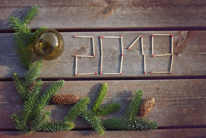 Επιγραφή 2019, φιαγμένη επάνω από αντιστοιχίες σε ένα ξύλινο υπόβαθρο με έναν πράσινο κλάδο ενός χριστουγεννιάτικου δέντρου στοκ εικόνες