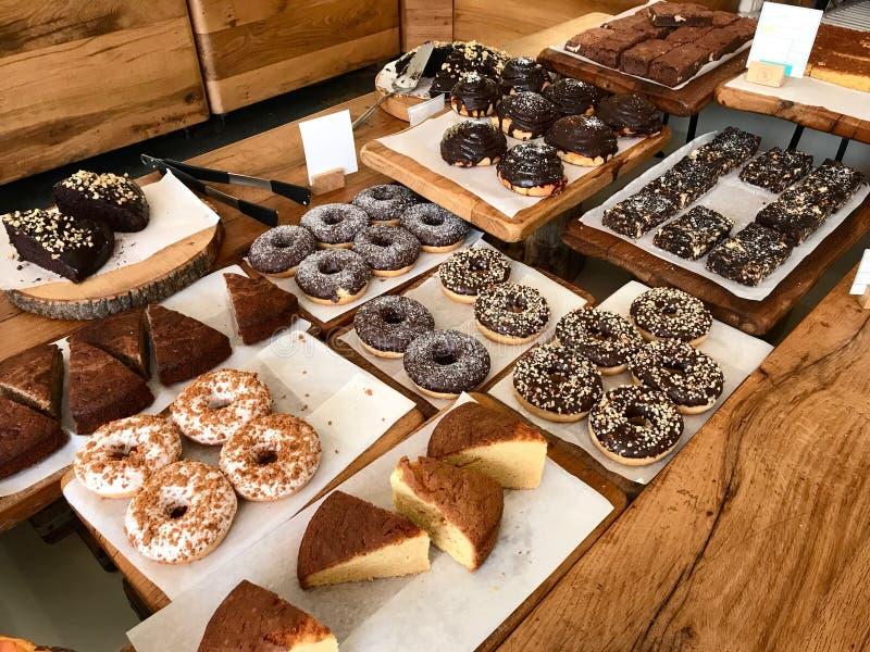 Επιδόρπια για την πώληση στην επίδειξη με Donuts, κουλούρια, Brownies, κέικ στην ξύλινη επιφάνεια στην προθήκη καταστημάτων καφέδ στοκ εικόνες με δικαίωμα ελεύθερης χρήσης