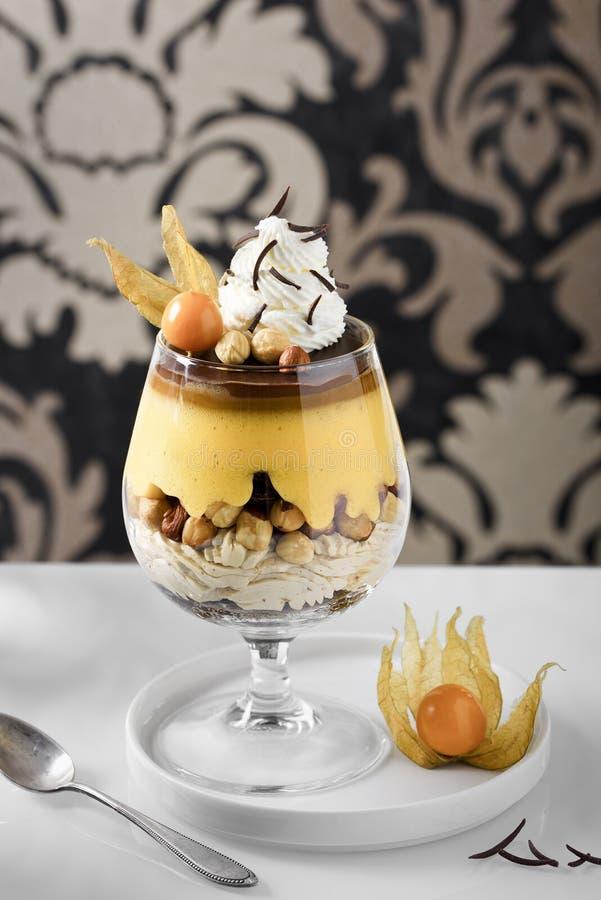 Επιδόρπιο με τα καρύδια, τη σοκολάτα και την κτυπημένη κρέμα σε ένα αναδρομικό υπόβαθρο στοκ εικόνα με δικαίωμα ελεύθερης χρήσης