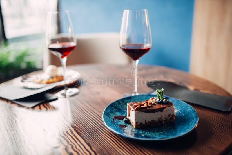 Επιδόρπιο στο πιάτο και κόκκινο κρασί στο γυαλί, κανένα στοκ εικόνες
