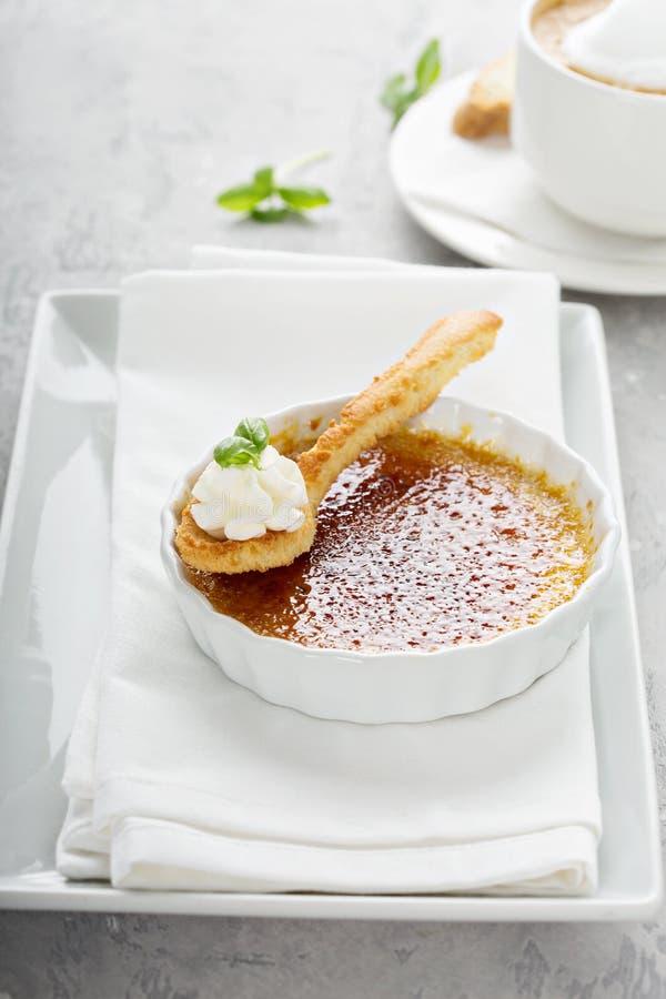 Επιδόρπιο creme brulle με ένα φλυτζάνι του cappuccino στοκ εικόνες