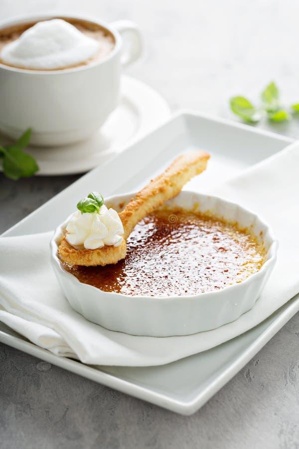 Επιδόρπιο creme brulle με ένα φλυτζάνι του cappuccino στοκ φωτογραφία με δικαίωμα ελεύθερης χρήσης