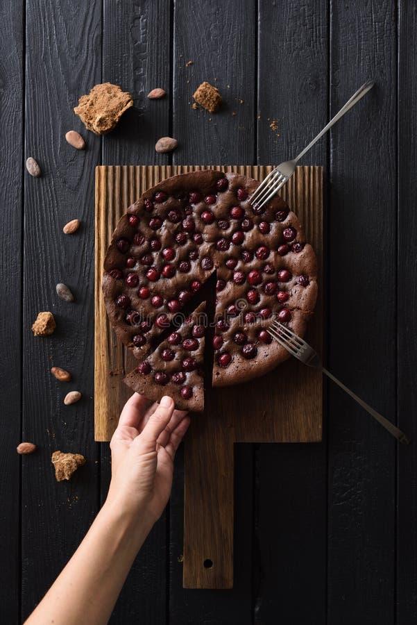 Επιεικές επιδόρπιο σοκολάτας Λεπτό χέρι γυναικών που φθάνει για το κέικ σοκολάτας με τα κεράσια και τη ζάχαρη καλάμων στη μαύρη τ στοκ εικόνες