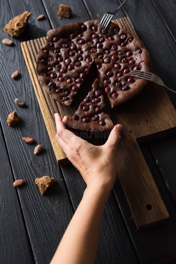 Επιεική τρόφιμα Λεπτό χέρι γυναικών που φθάνει για την πίτα σοκολάτας με τα κεράσια στο σκοτεινό υπόβαθρο στοκ φωτογραφία με δικαίωμα ελεύθερης χρήσης