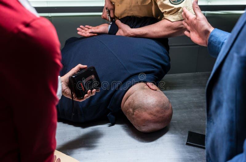Επιθετικός κατηγορούμενος που δένεται με χειροπέδες από τον αστυνομικό κατά τη διάρκεια της προκαταρκτικής ακρόασης στοκ εικόνες με δικαίωμα ελεύθερης χρήσης