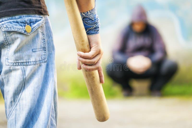 Επιθετικό άτομο με ένα ρόπαλο του μπέιζμπολ ενάντια σε άλλο άτομο στοκ εικόνα με δικαίωμα ελεύθερης χρήσης