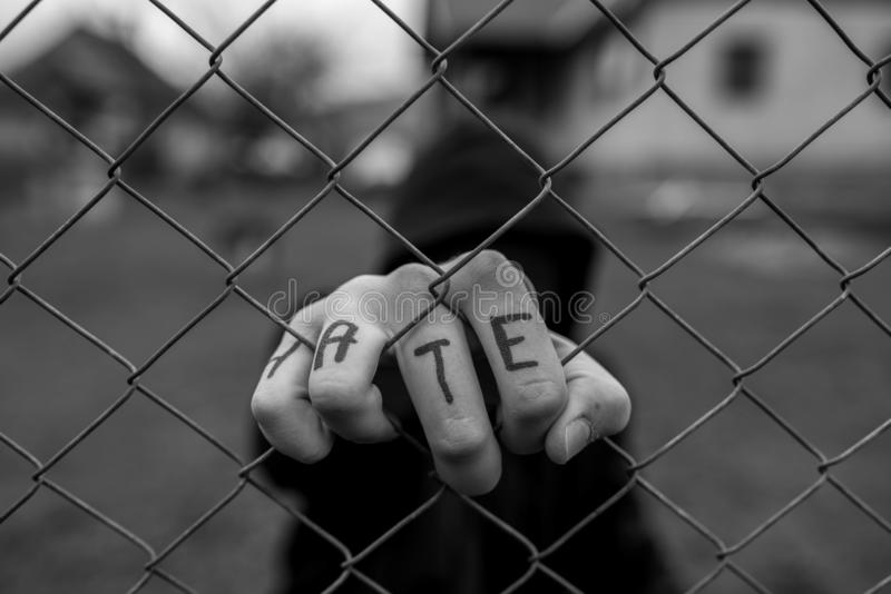 Επιθετικό έφηβο αγόρι που κρατά τον καλωδιωμένο φράχτη στο σωφρονιστικό ινστιτούτο, η λέξη μίσος γράφεται στο χέρι του στοκ φωτογραφία με δικαίωμα ελεύθερης χρήσης
