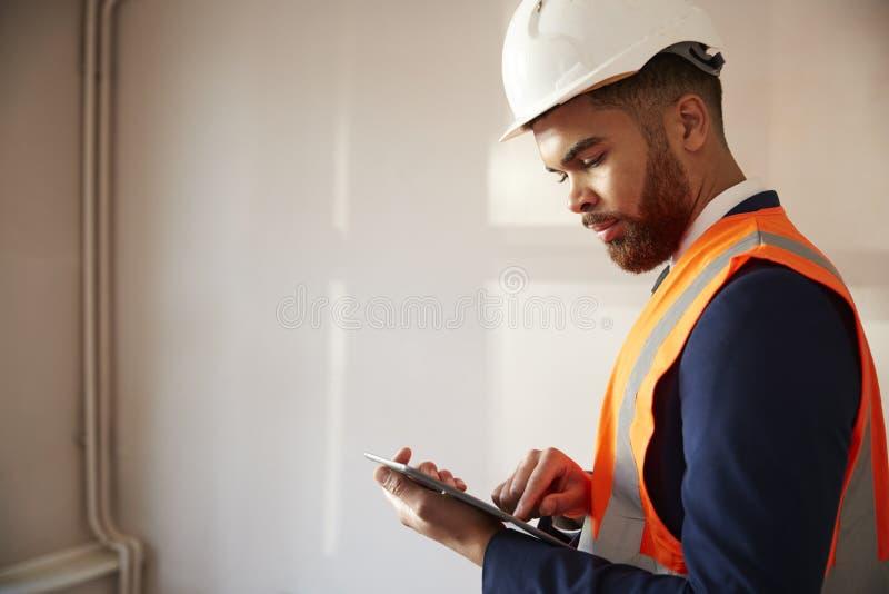Επιθεωρητής στο σκληρό καπέλο και υψηλό σακάκι διαφάνειας με την ψηφιακή ταμπλέτα που πραγματοποιεί την επιθεώρηση σπιτιών στοκ φωτογραφίες