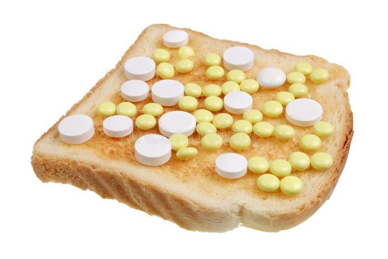 Επικίνδυνη έννοια τροφίμων - το σάντουιτς φρυγανιάς με τα ιατρικά χάπια στοκ φωτογραφία με δικαίωμα ελεύθερης χρήσης