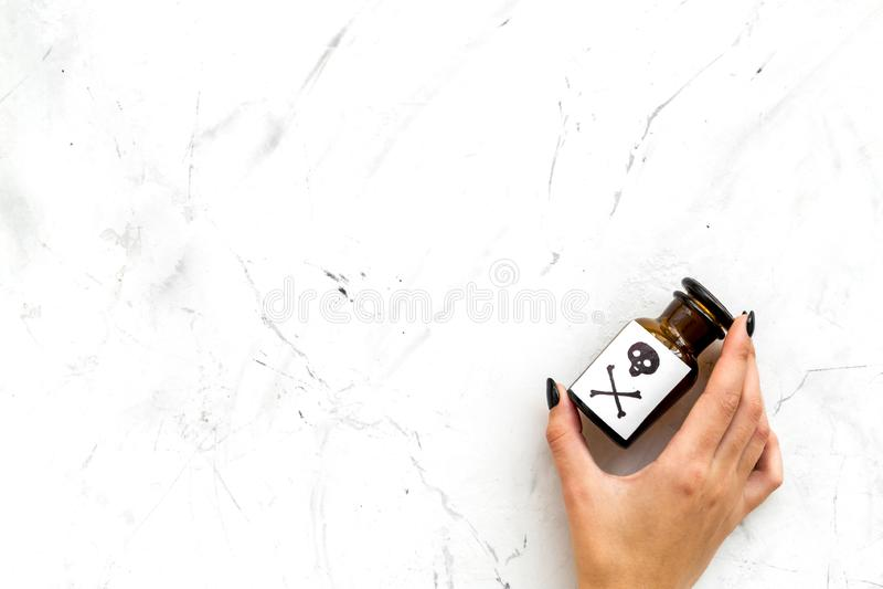 Επικίνδυνοι εθισμοί, επικίνδυνη ψυχαγωγία δηλητήριο Θηλυκό μπουκάλι λαβής χεριών με το κρανίο και crossbones στην άσπρη πέτρα στοκ εικόνες με δικαίωμα ελεύθερης χρήσης