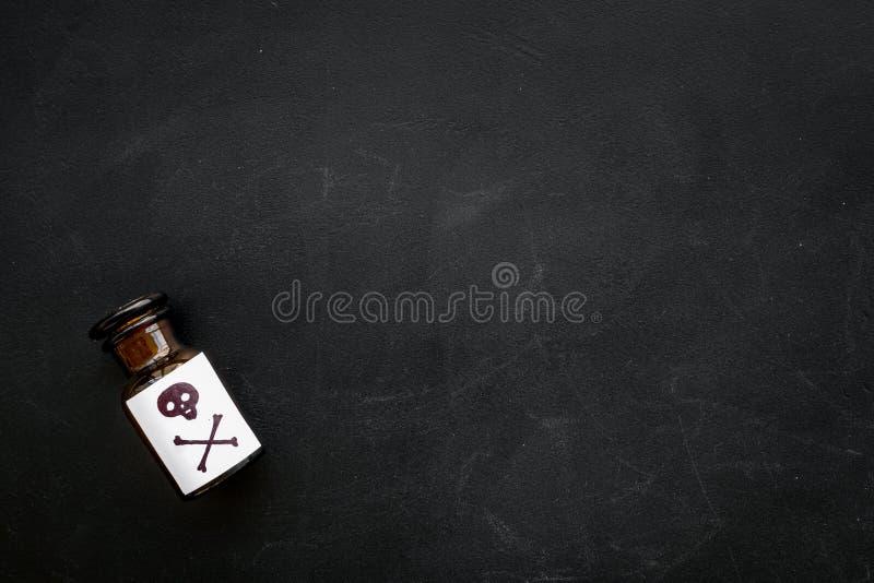Επικίνδυνοι εθισμοί, επικίνδυνη ψυχαγωγία δηλητήριο Μπουκάλι με το κρανίο και crossbones στη μαύρη τοπ άποψη υποβάθρου στοκ φωτογραφία με δικαίωμα ελεύθερης χρήσης