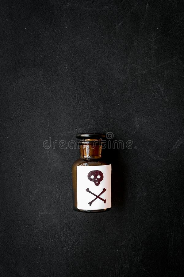 Επικίνδυνοι εθισμοί, επικίνδυνη ψυχαγωγία δηλητήριο Μπουκάλι με το κρανίο και crossbones στη μαύρη τοπ άποψη υποβάθρου στοκ εικόνες