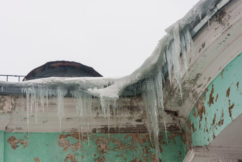 Επικίνδυνα παγάκια σε μια στέγη σπιτιών στοκ εικόνες με δικαίωμα ελεύθερης χρήσης