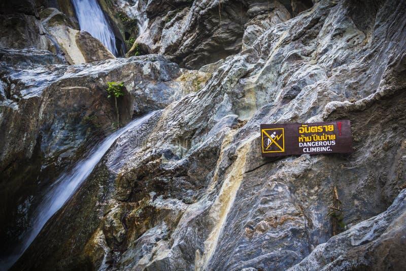 Επικίνδυνη αναρρίχηση προειδοποιητικών σημαδιών στον καταρράκτη με τις πέτρες στοκ φωτογραφίες